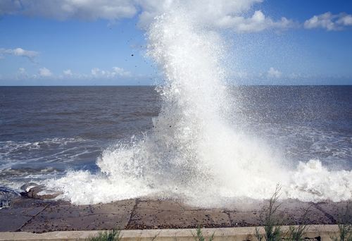 Waves hit sea wall illustrating hydraulic action and corrasion coastal erosion, East Lane, Bawdsey,